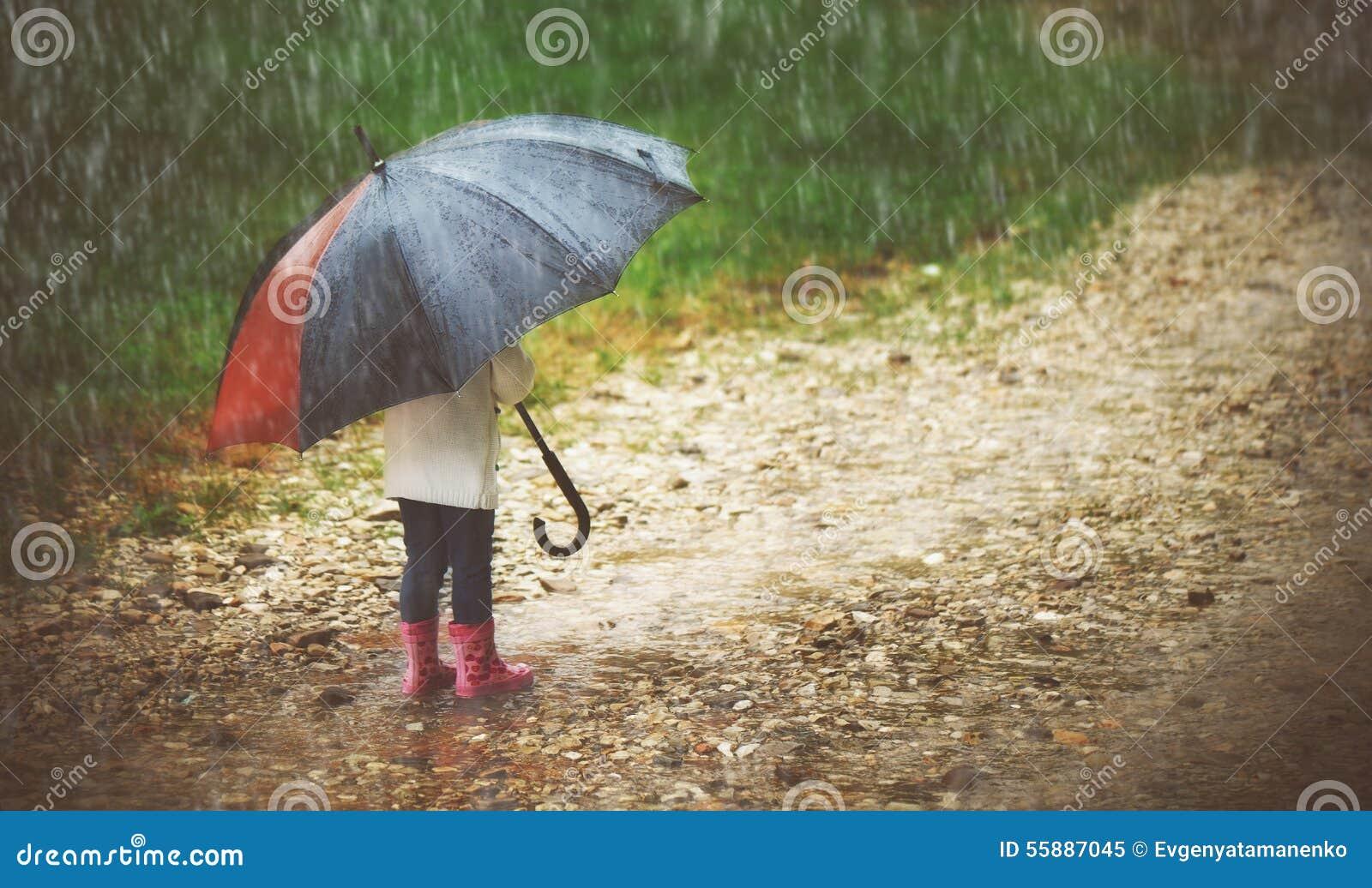Lyckligt behandla som ett barn flickan med paraplyet i regnkörningarna igenom