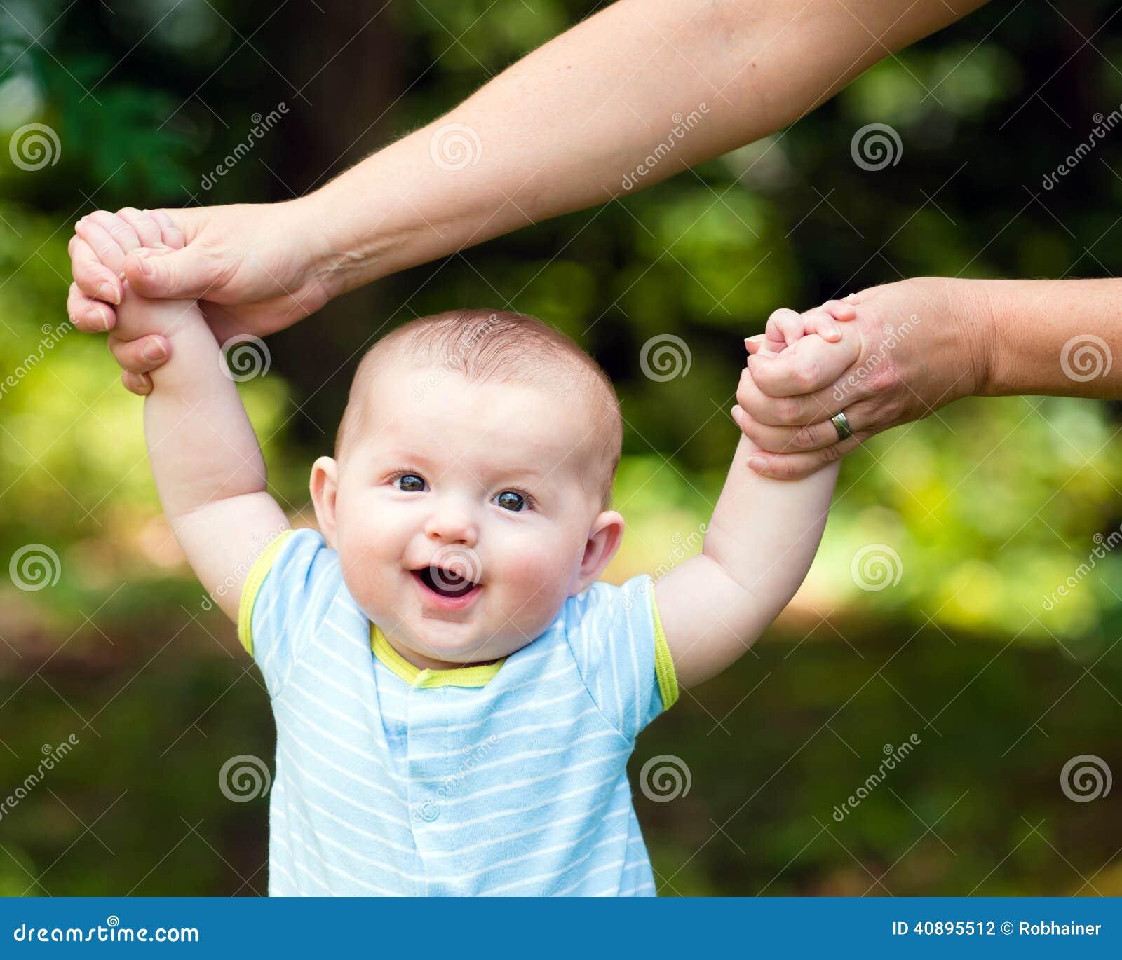 Lyckligt behandla som ett barn pojken som lär att gå på gräs