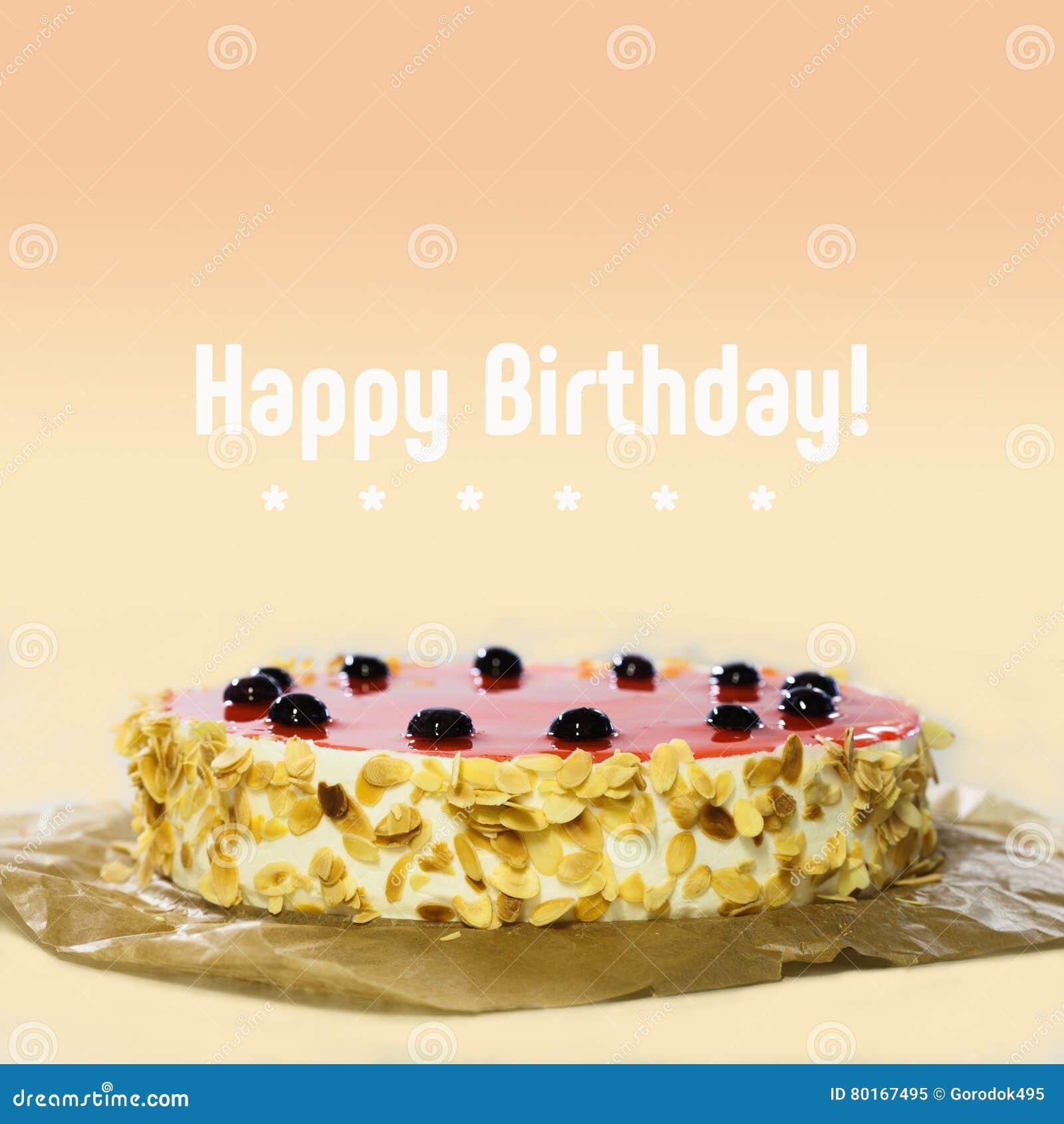 Lyckligt födelsedagkort Baka ihop med den svarta körsbäret, röd gelé, mandelflingor Söt efterrätt på bakgrund för persikafärglutn