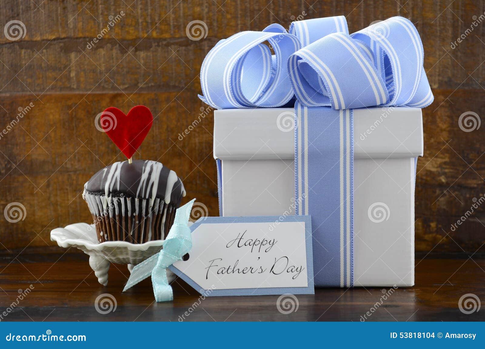 Lyckligt faderbegrepp med den blåa och vita gåvan och muffin