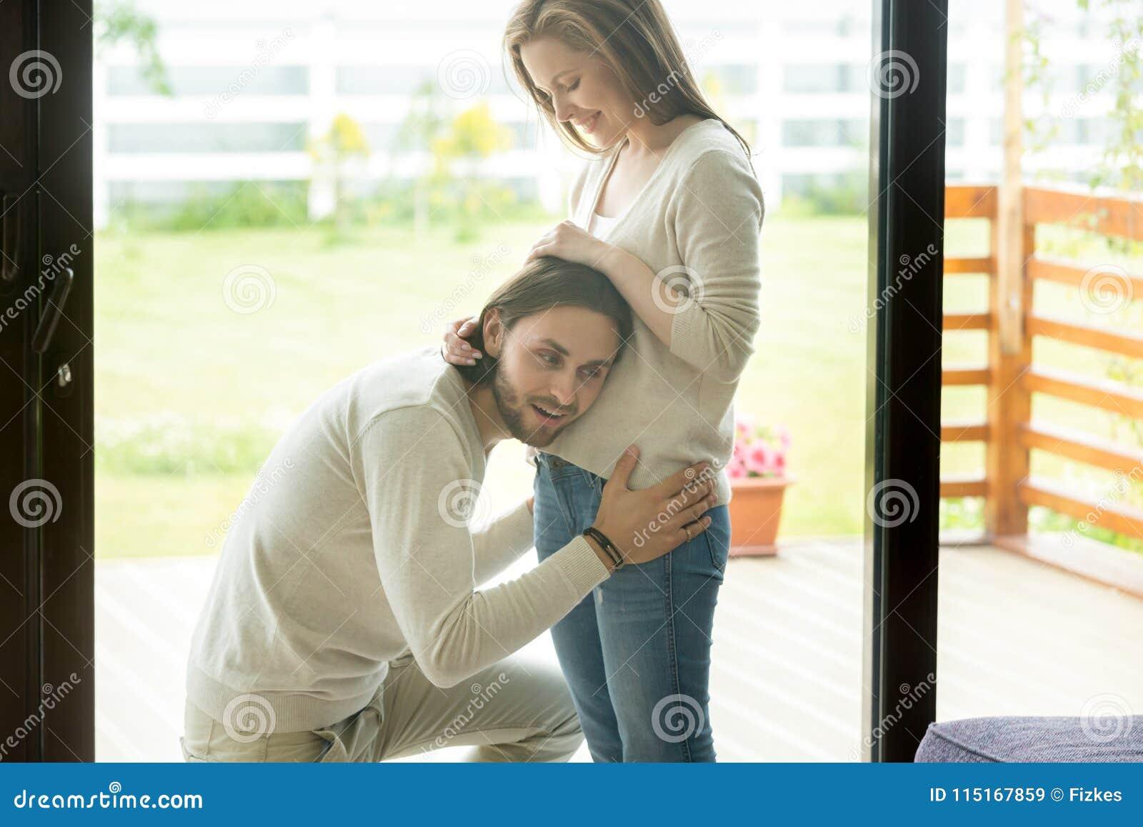 Lyckligt farsa-till-var sätter örat till den gravida buken, havandeskap och män