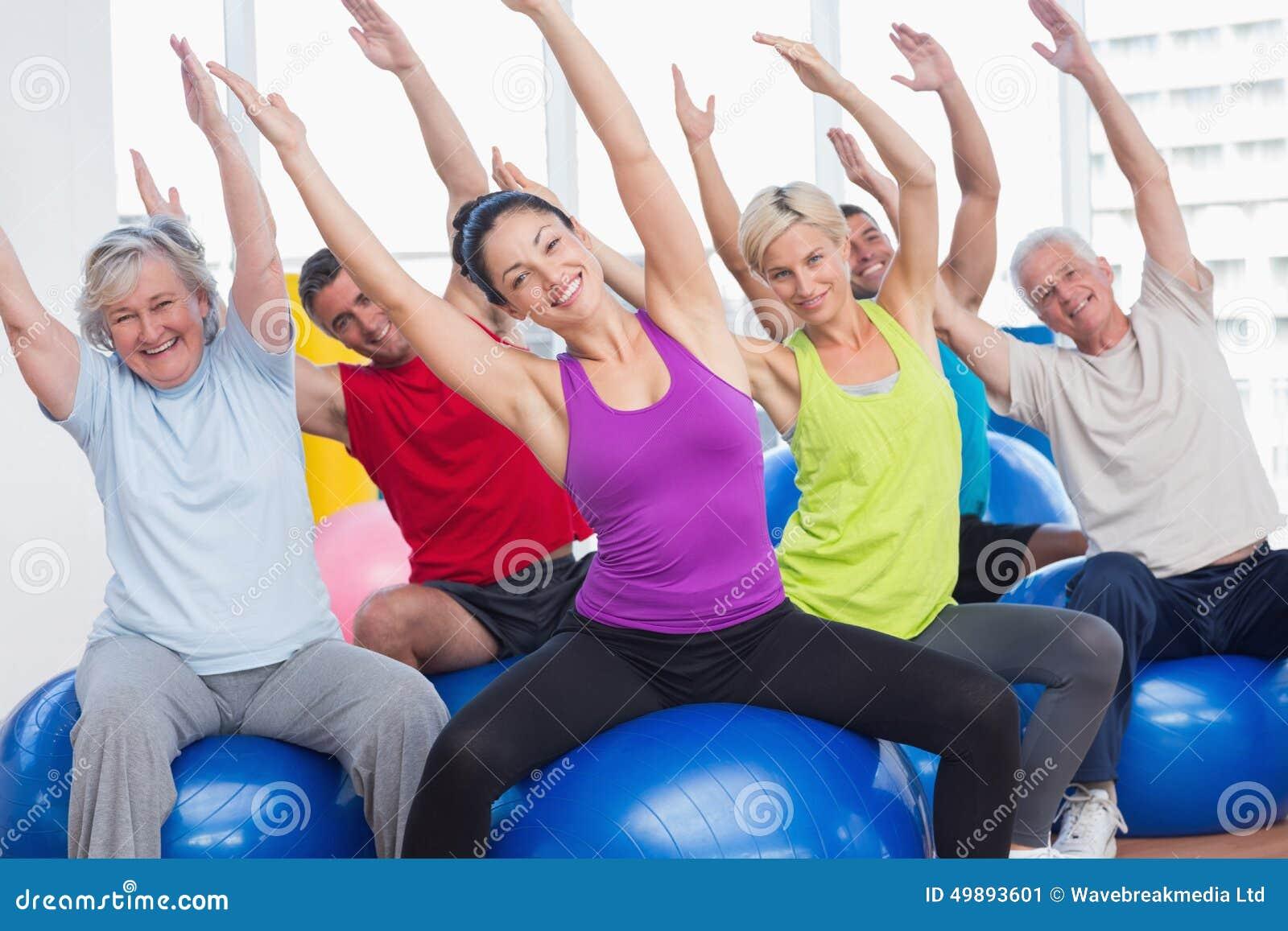 Lyckligt folk som övar i idrottshallgrupp