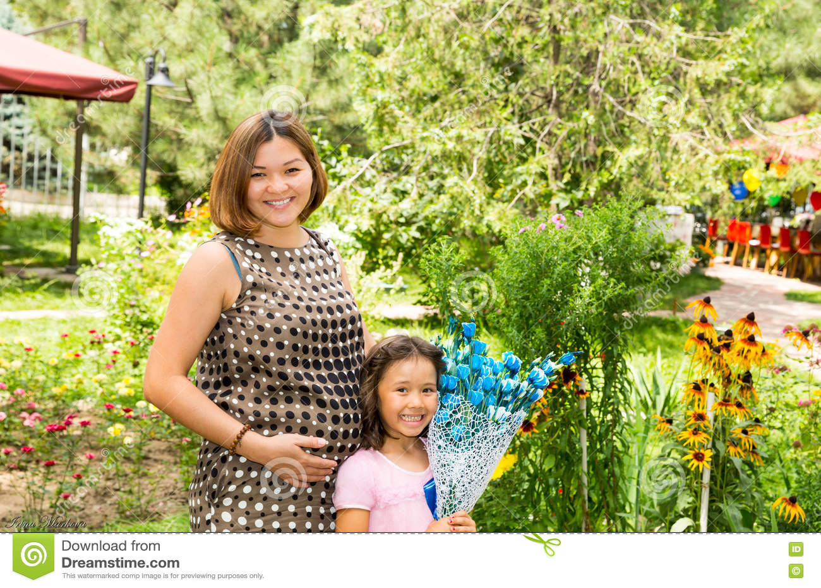 Lyckligt gravid asiatiskt krama för mamma- och barnflicka Begreppet av barndom och familjen