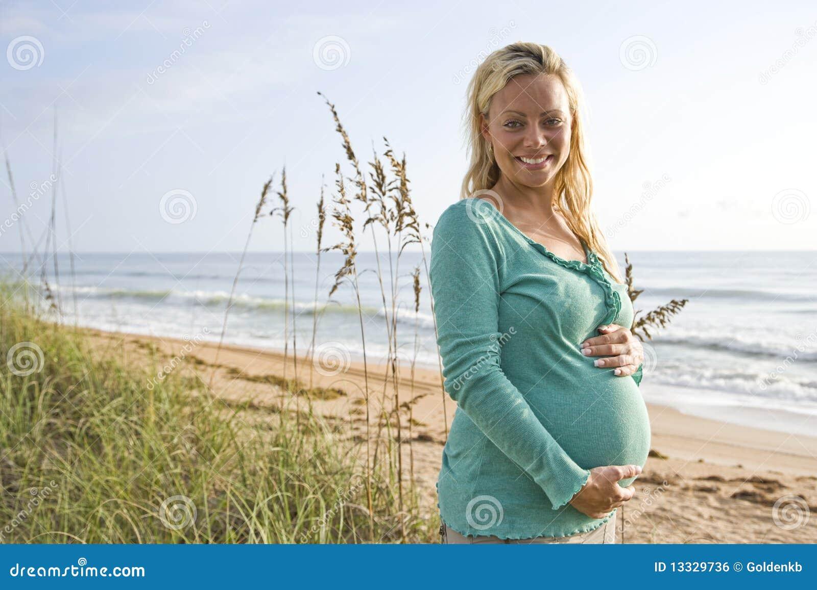 Lyckligt gravid plattform kvinnabarn för strand