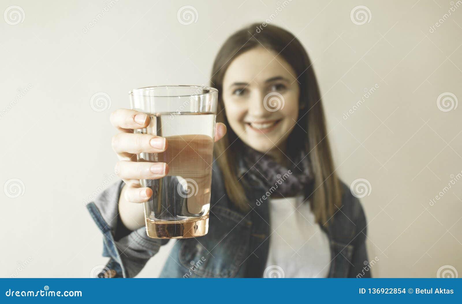 Lyckligt härligt dricksvatten för ung kvinna