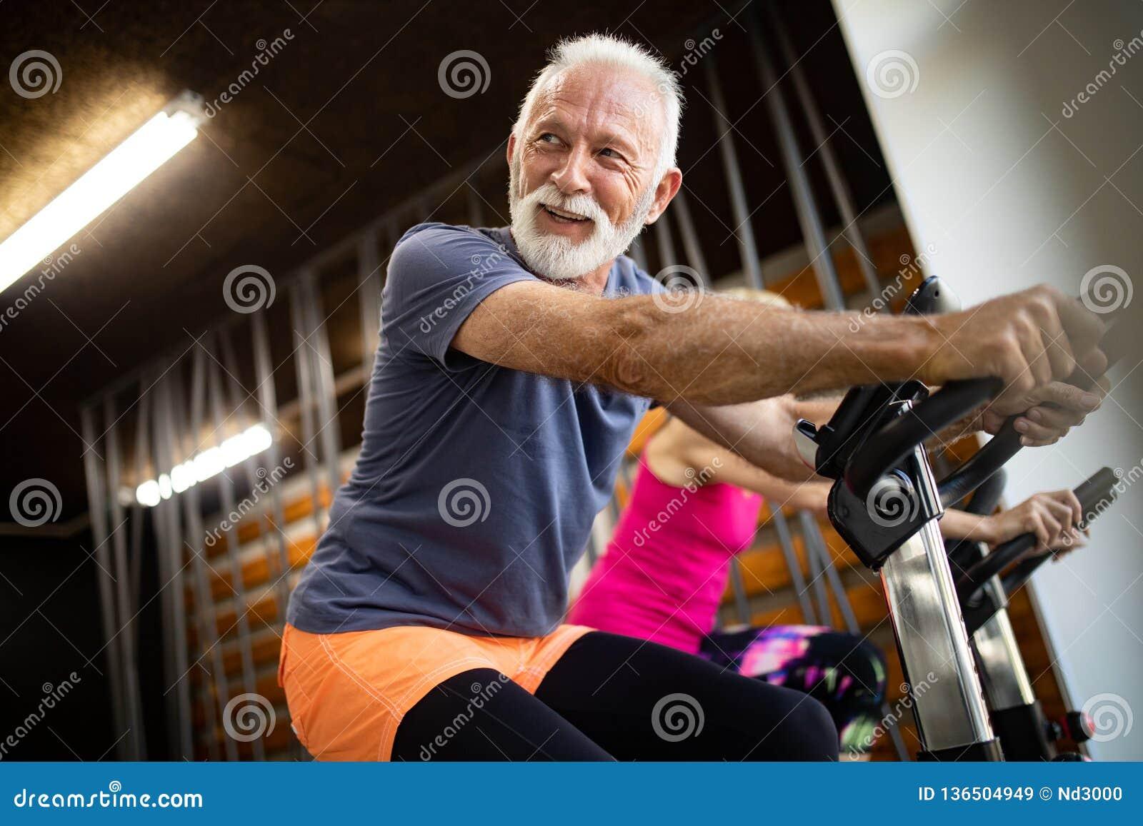 Lyckligt högt folk som gör övningar i idrottshall för att bli färdigt