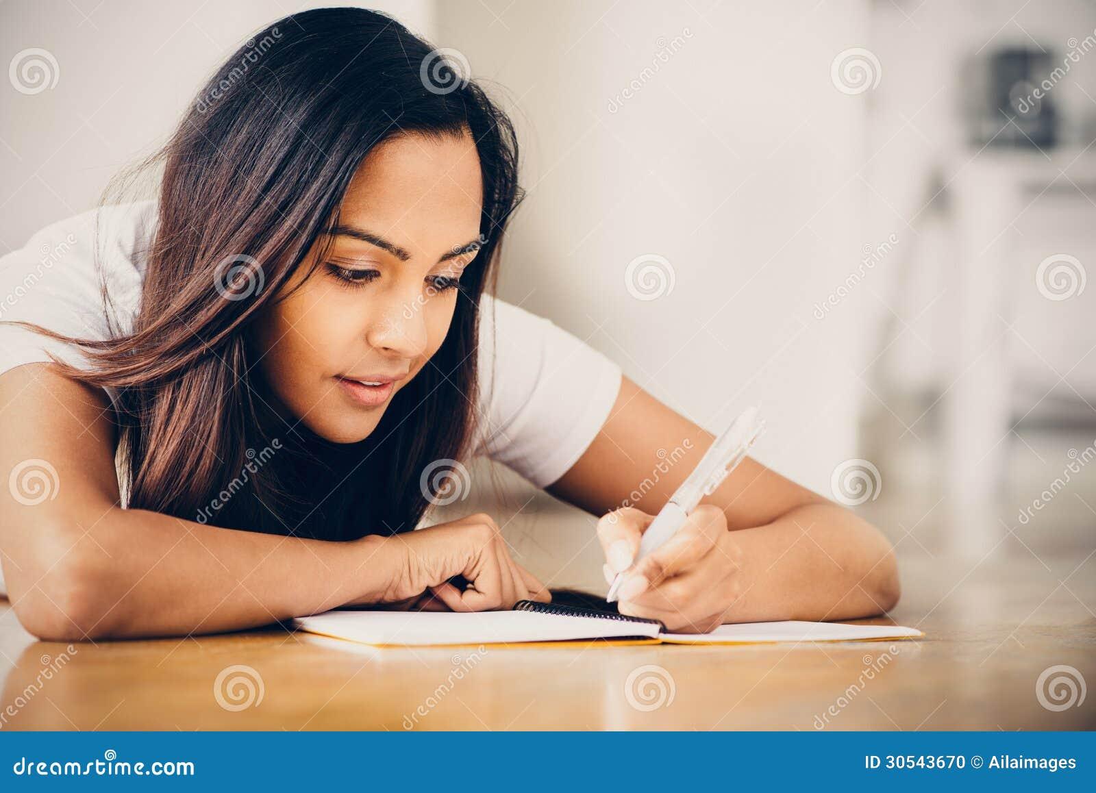 Lyckligt indiskt studera för handstil för utbildning för kvinnastudent