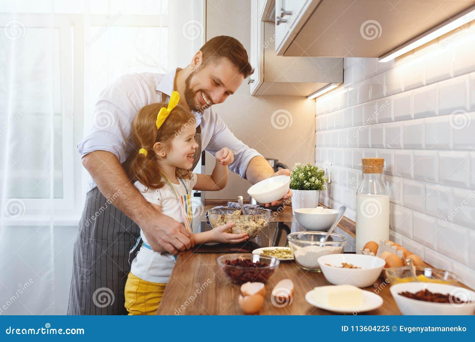 Lyckligt kök för familj Fader- och barndottern knådar deg a