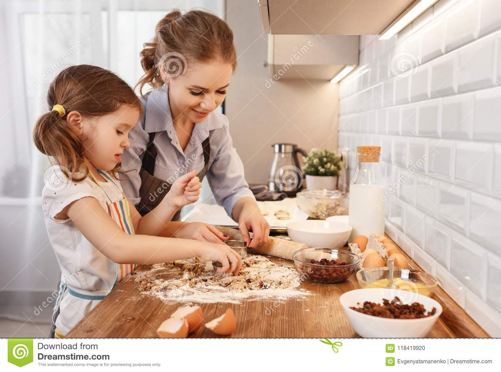Lyckligt kök för familj stekheta kakor för moder- och barndotter