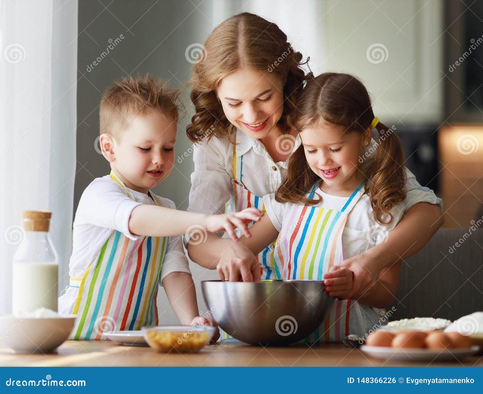 Lyckligt k?k f?r familj modern och barn som f?rbereder deg, bakar kakor