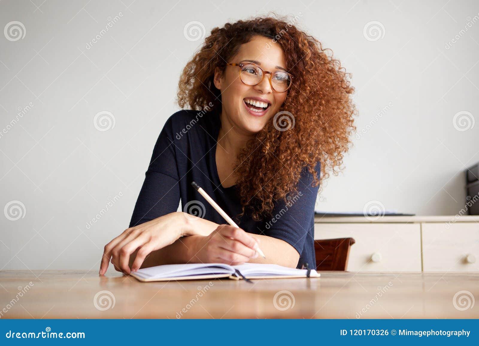 Lyckligt kvinnligt högskolestudentsammanträde på skrivbordhandstil i bok