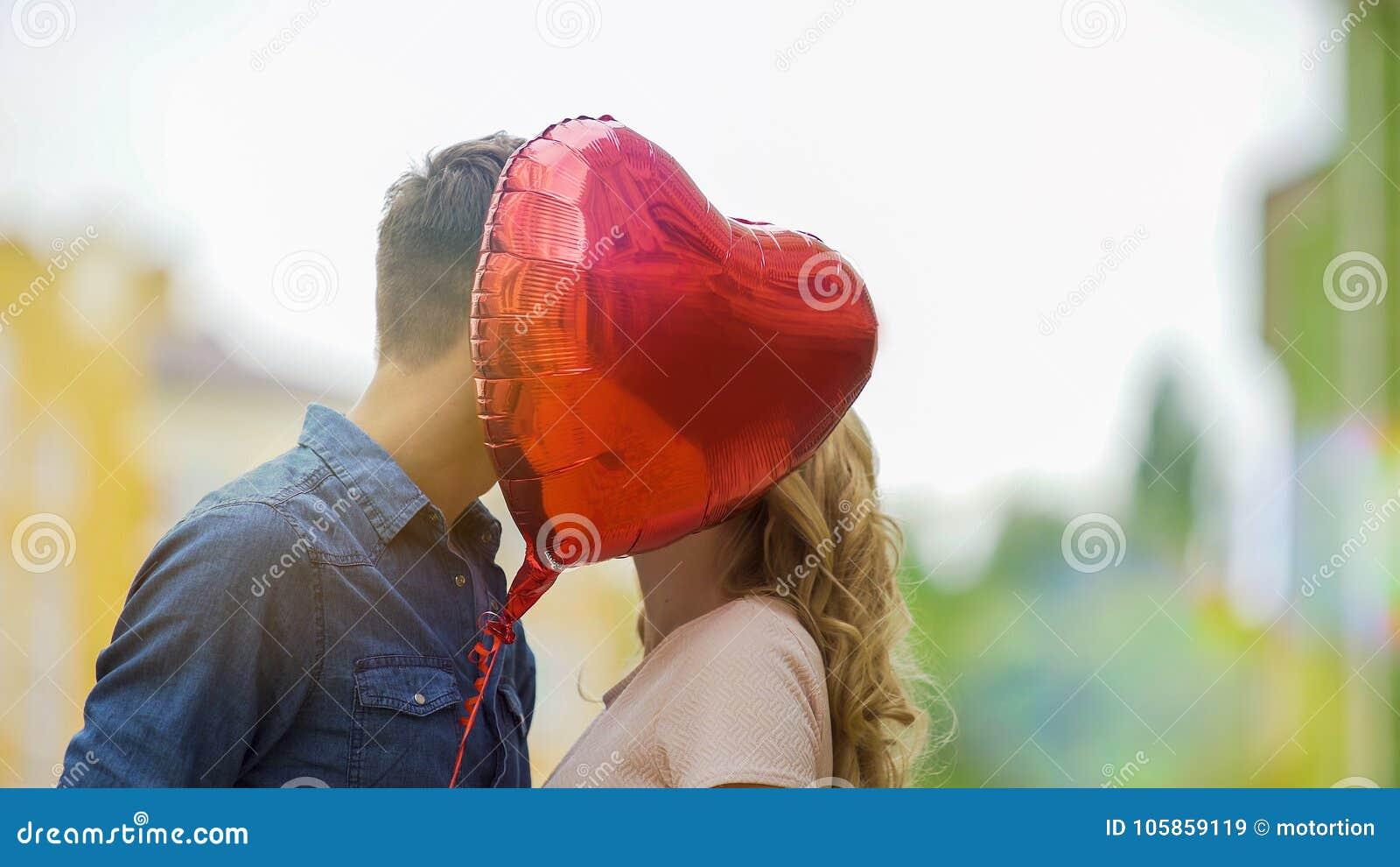 Lyckligt kyssa för par som döljer bak hjärtaballongen, romantiskt förhållande, datum