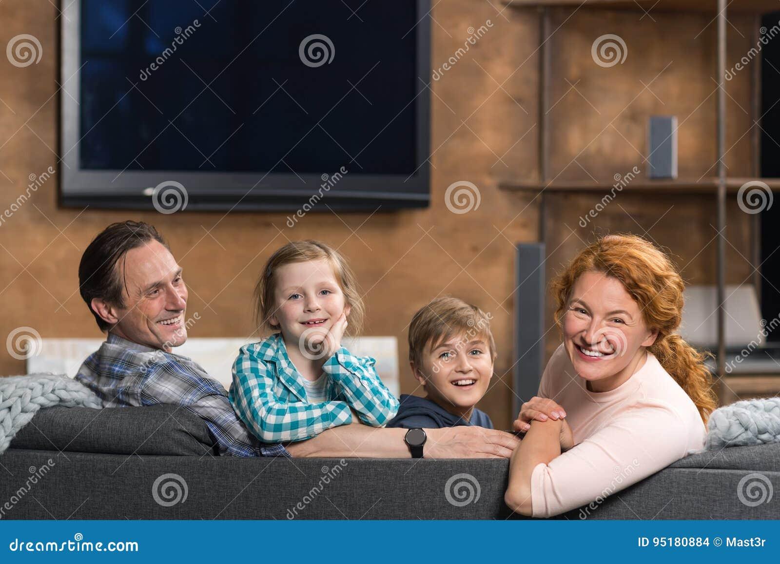 Lyckligt le familjsammanträde på soffan i vardagsrum, förälderpar med två barn