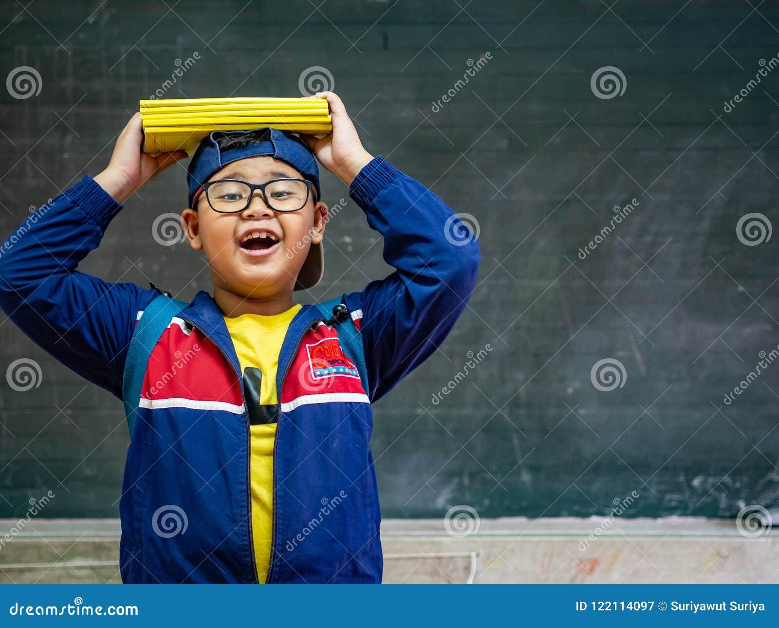 Lyckligt le och ställning för pojkekläderexponeringsglas framme av blackboen