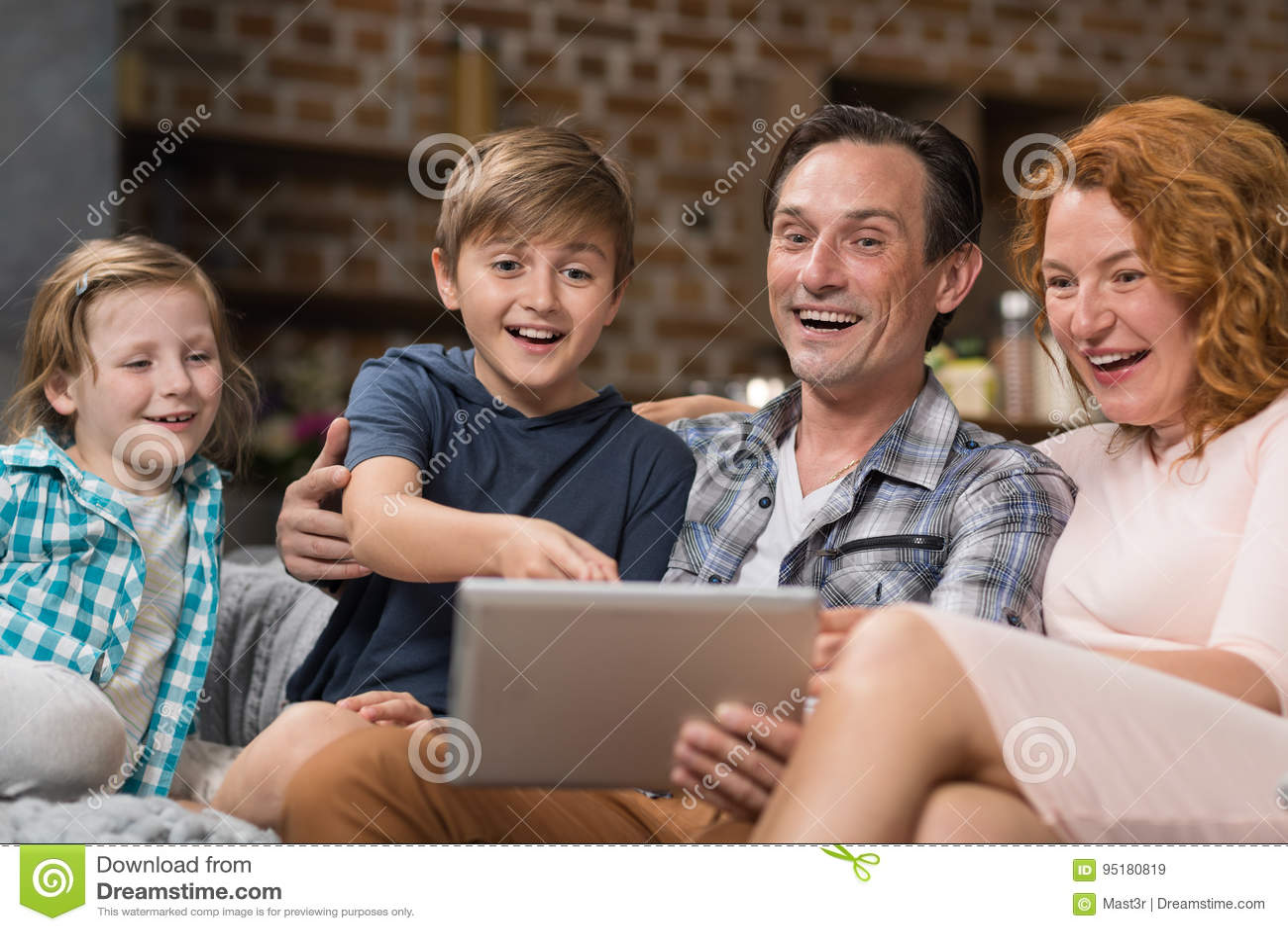 Lyckligt le sammanträde för dator för familjbruksminnestavla på soffan i vardagsrum, föräldrar som spenderar Tid med sonen och do