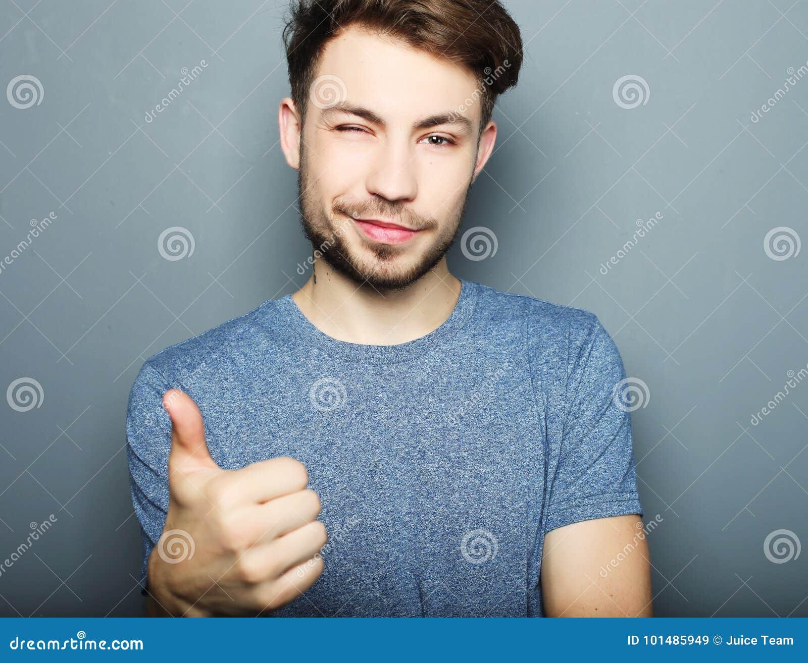 Lyckligt leende för stilig man, hållhand med det ok gesttecknet