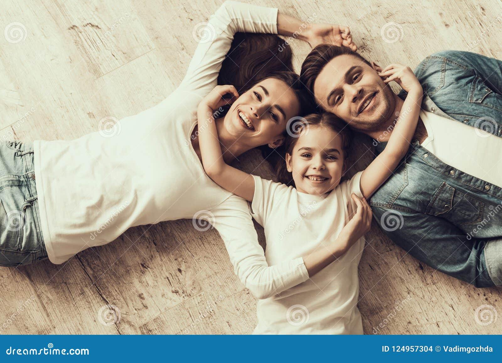 Lyckligt ligga för familj av golvet tillsammans hemma