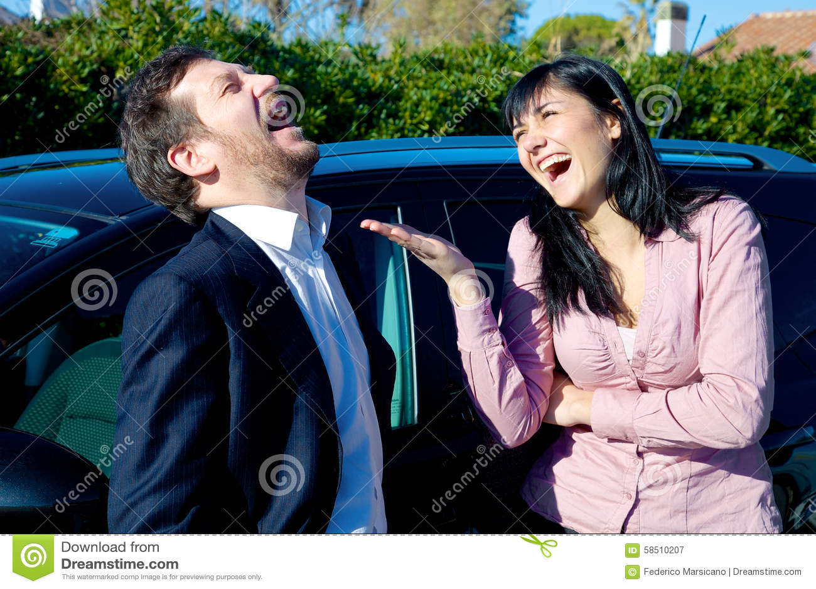 Lyckligt lyckat affärsfolk som framme skrattar av bilen