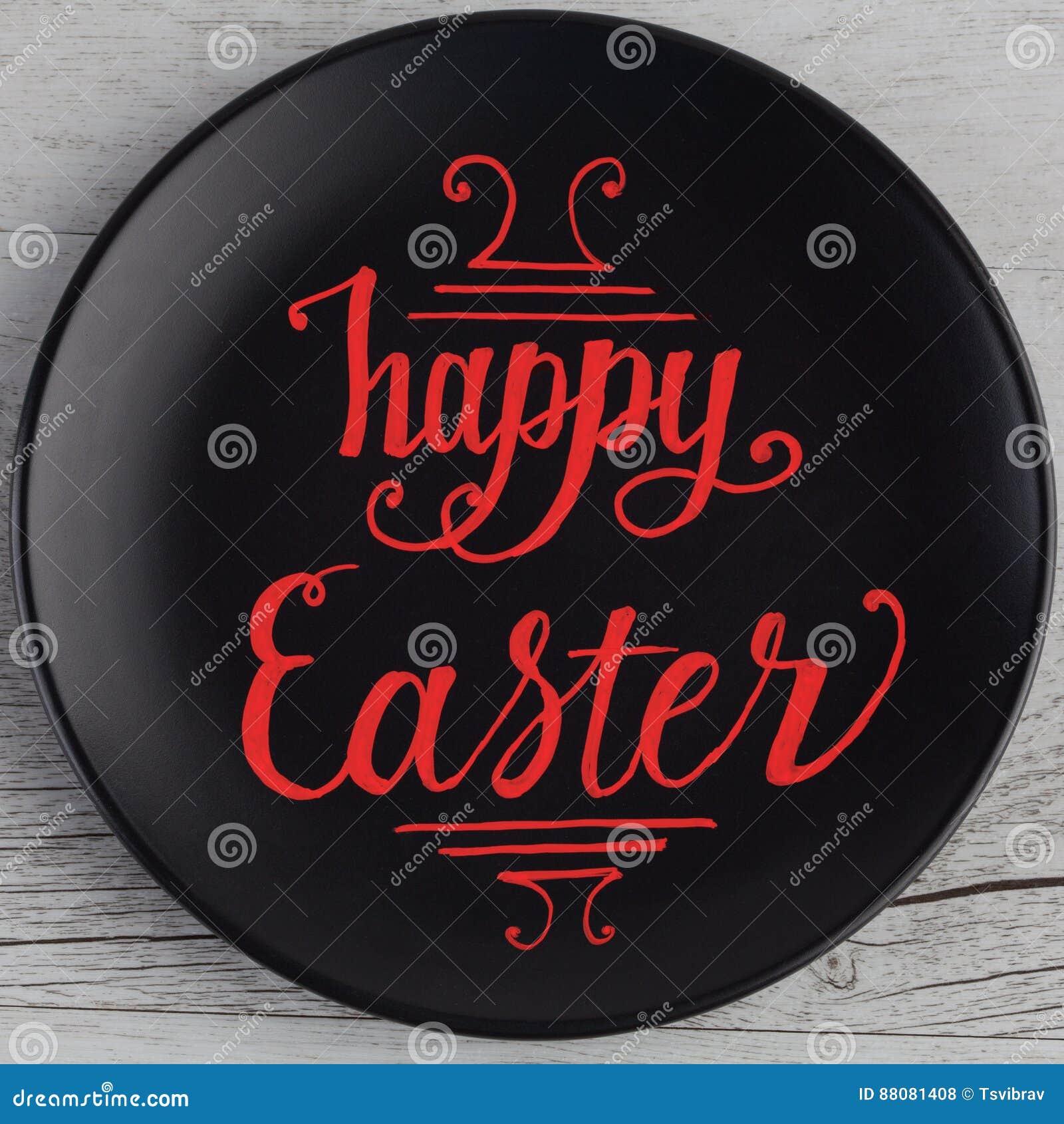 Lyckligt märka för påskhand som är skriftligt i rött på den svarta plattan och wh