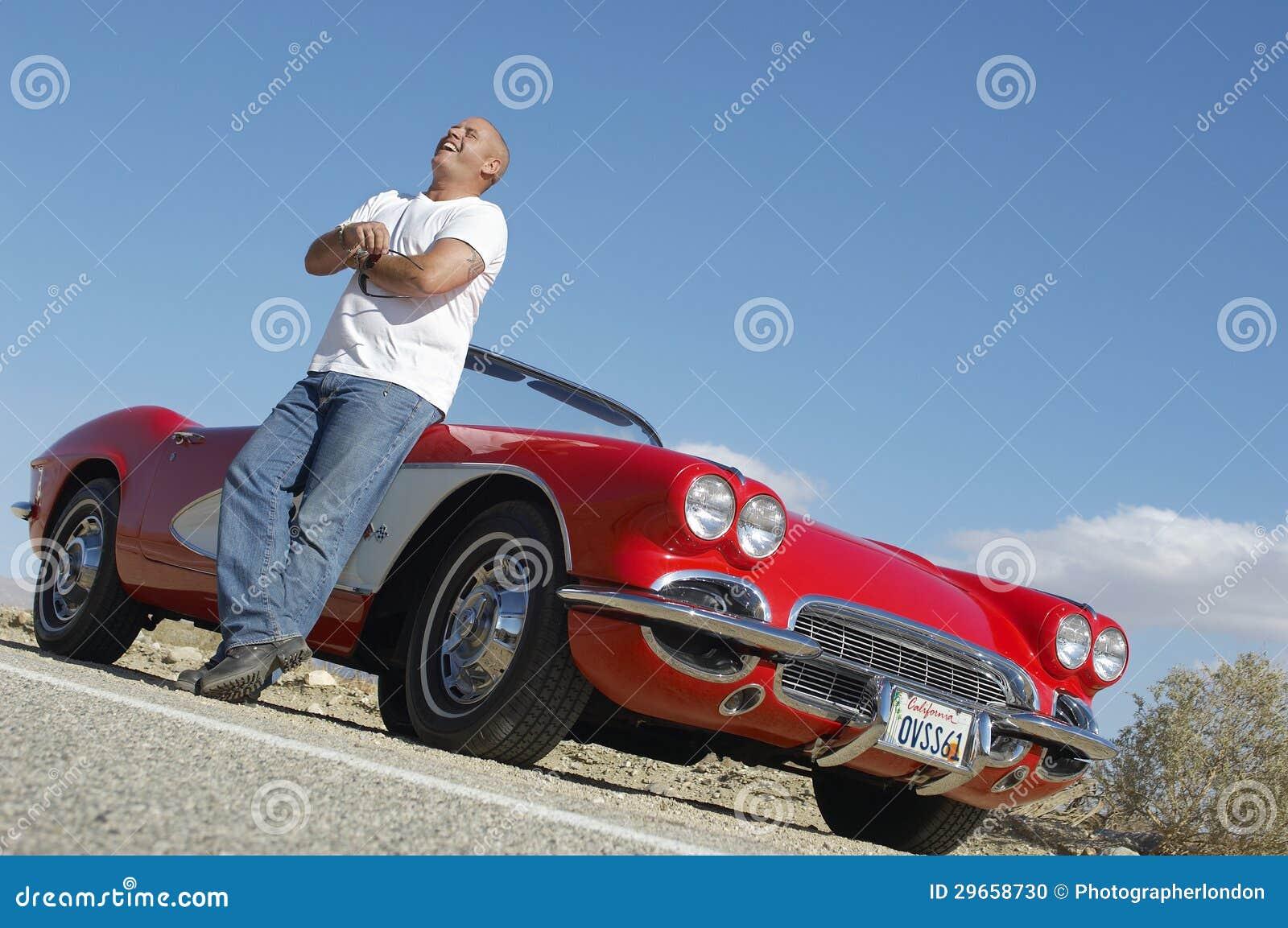 Lyckligt mananseende bredvid den klassiska bilen på vägen