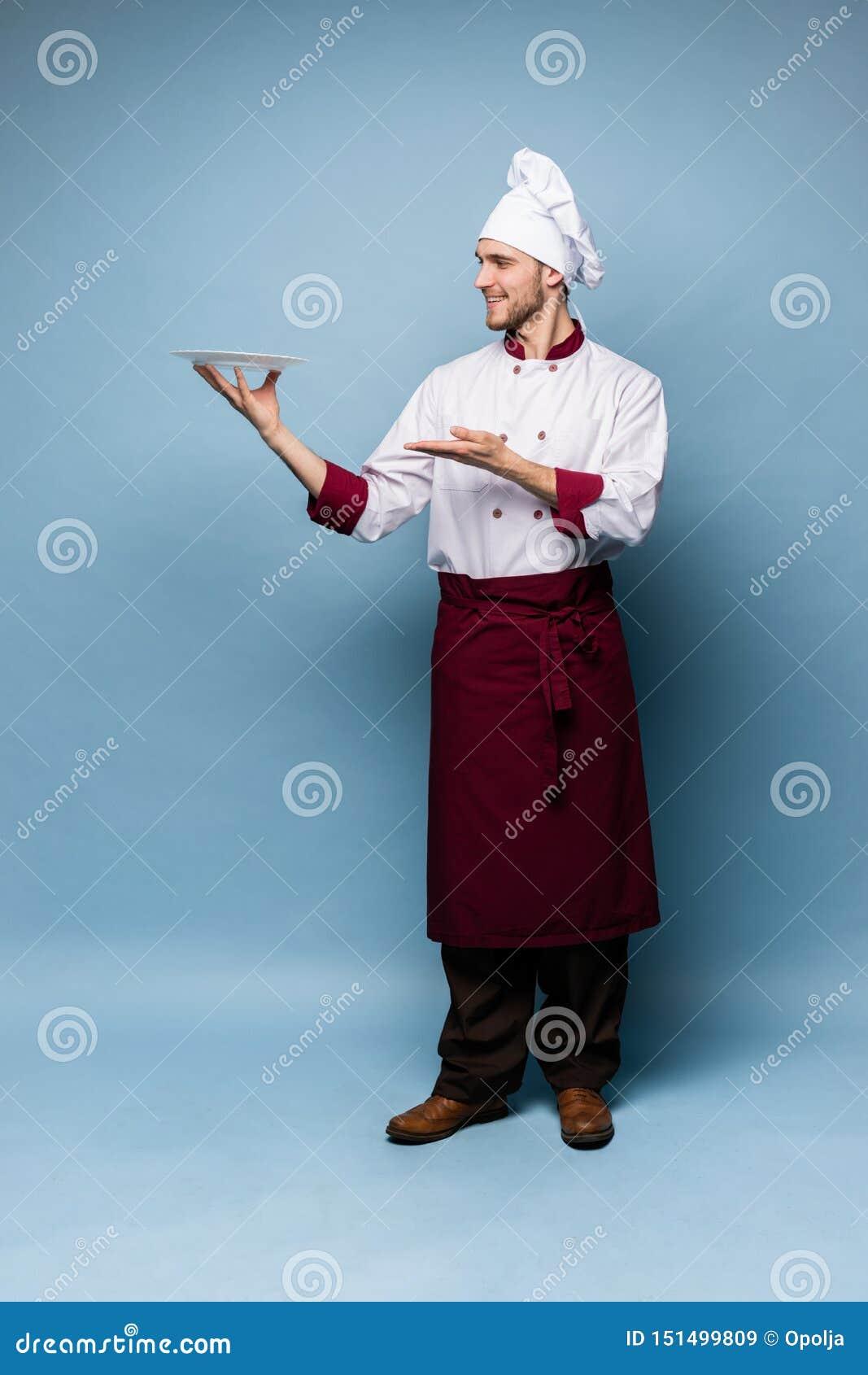 Lyckligt manligt kockkockanseende med plattan som isoleras på ljust - blå bakgrund