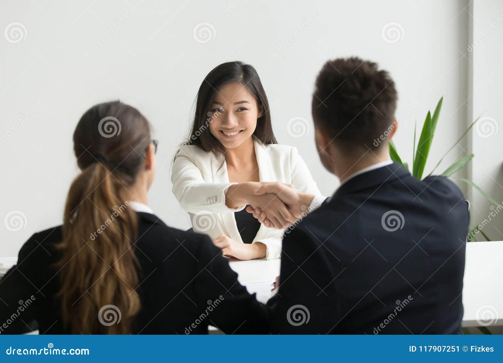Lyckligt millennial asiatiskt sökande som får hyrt skaka handen av H