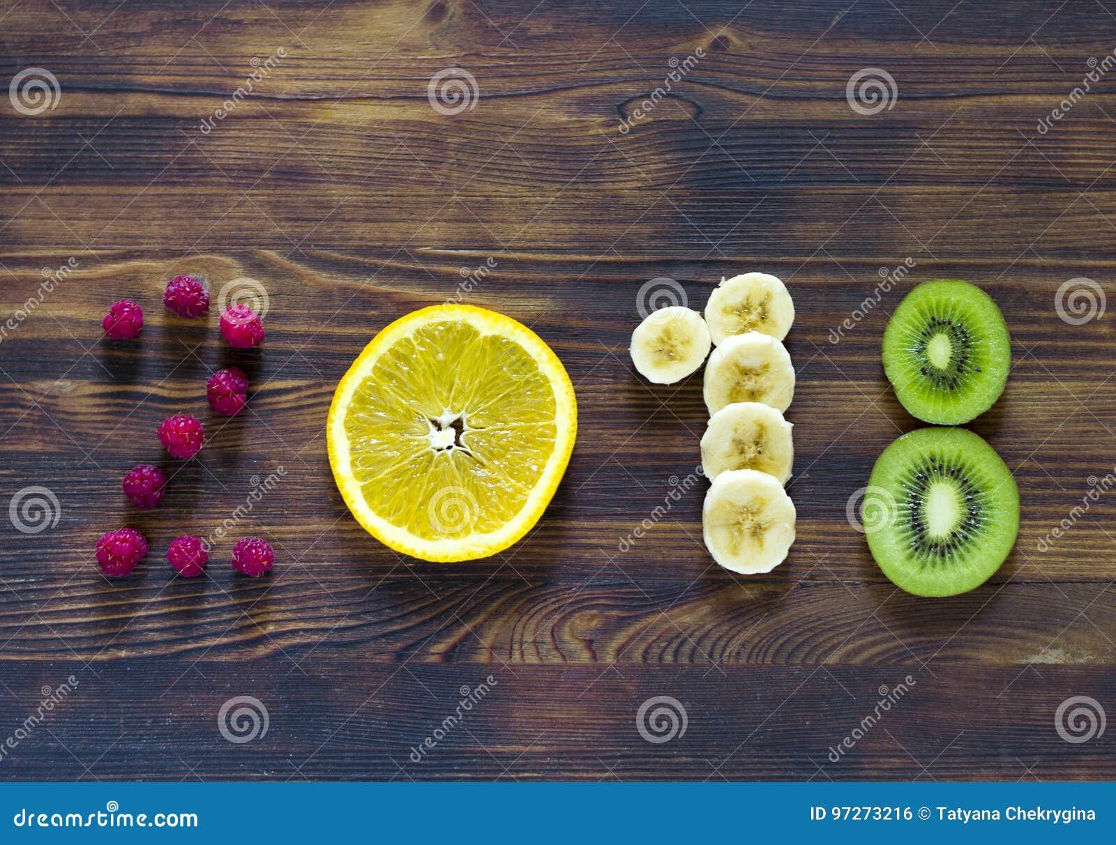 Lyckligt nytt år 2018 av frukt och bär på träbakgrund