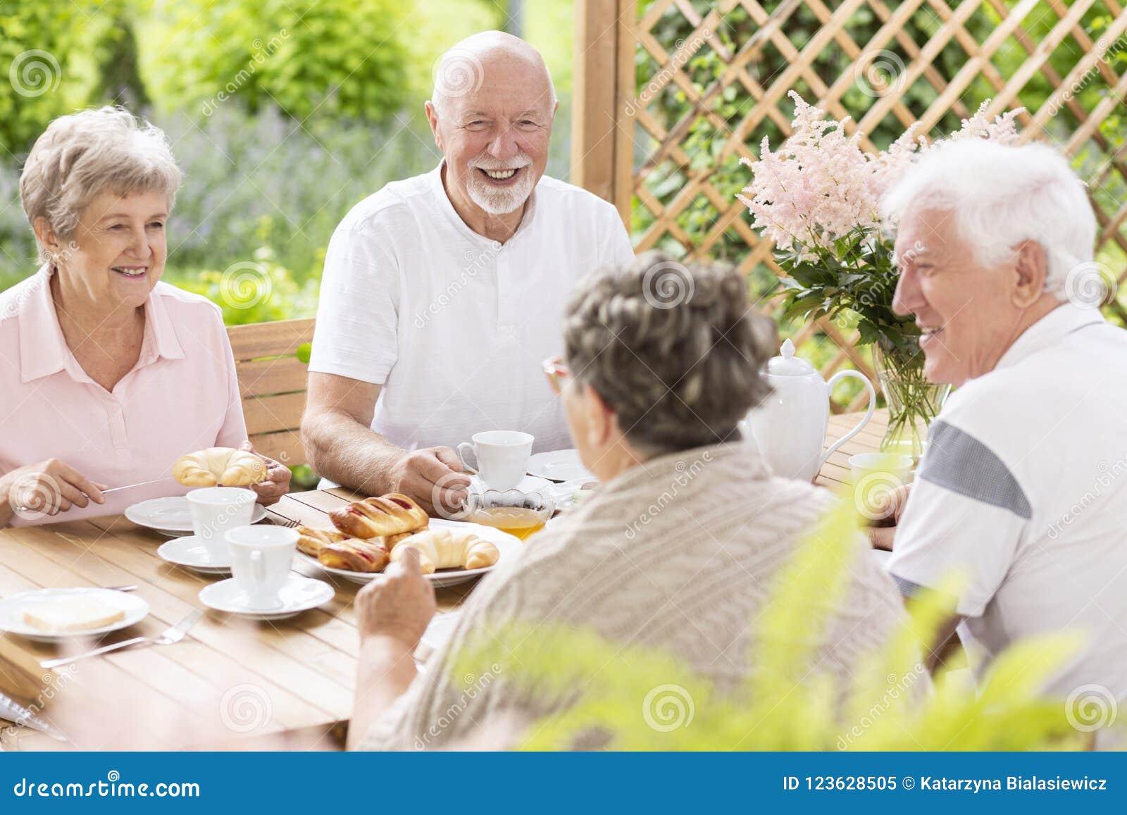 Lyckligt och le högt folk som har gyckel, medan äta breakfas