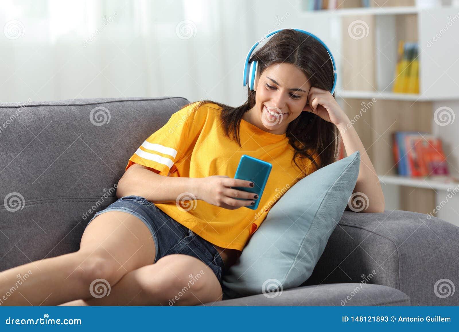 Lyckligt tonårigt lyssna till musik som hemma kontrollerar telefonen på en soffa