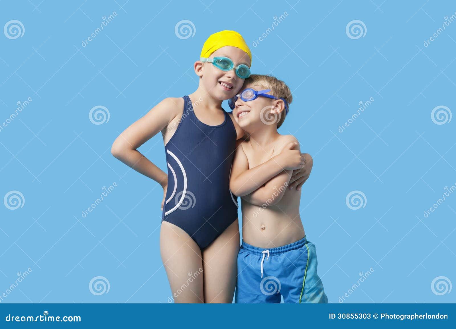 Lyckligt ungt syskon i swimwear med armen omkring över blå bakgrund