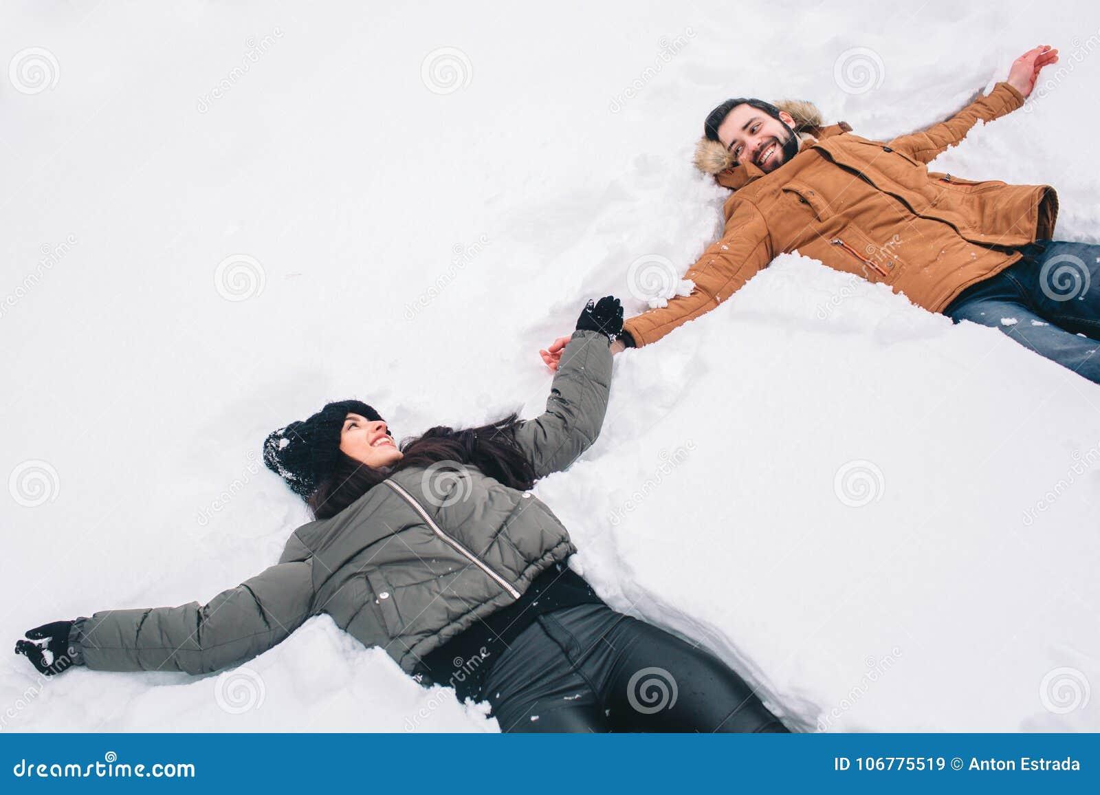 Lyckligt vinterbarn för par familj utomhus man och kvinna som ser uppåtriktade och skratta Förälskelse, gyckel, säsong och folk