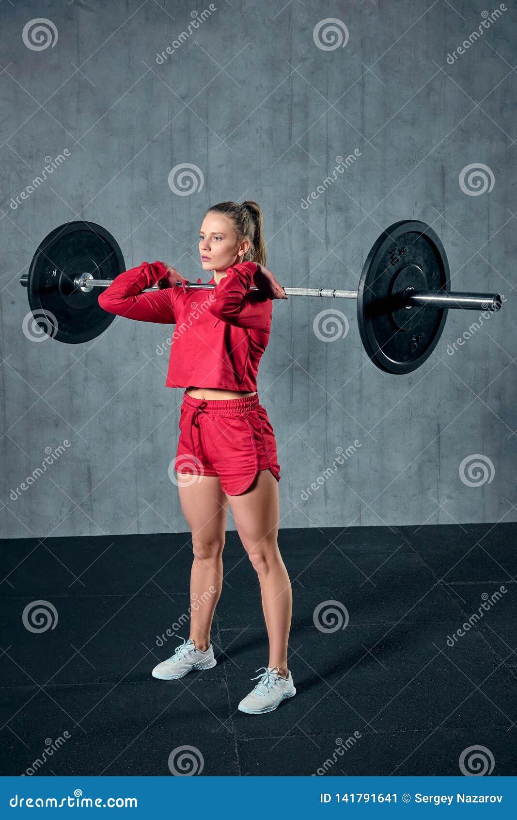 Lyftande skivstång för härlig konditionkvinna Lyftande vikter för sportig kvinna Färdig flicka som övar byggnadsmuskler