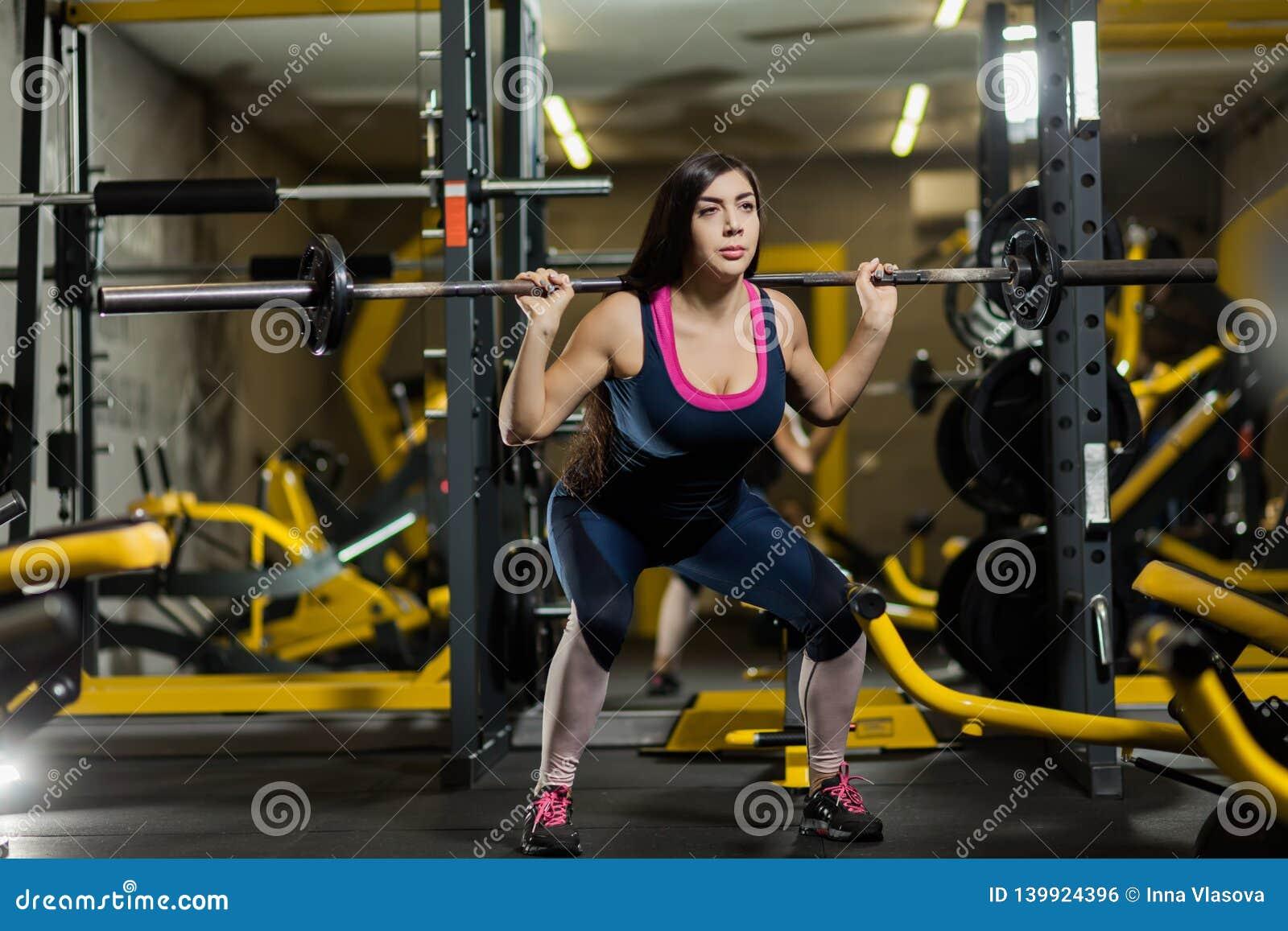 Lyftande vikter för sportig kvinna Färdig flicka som övar byggnadsmuskler Kondition och bodybuilding
