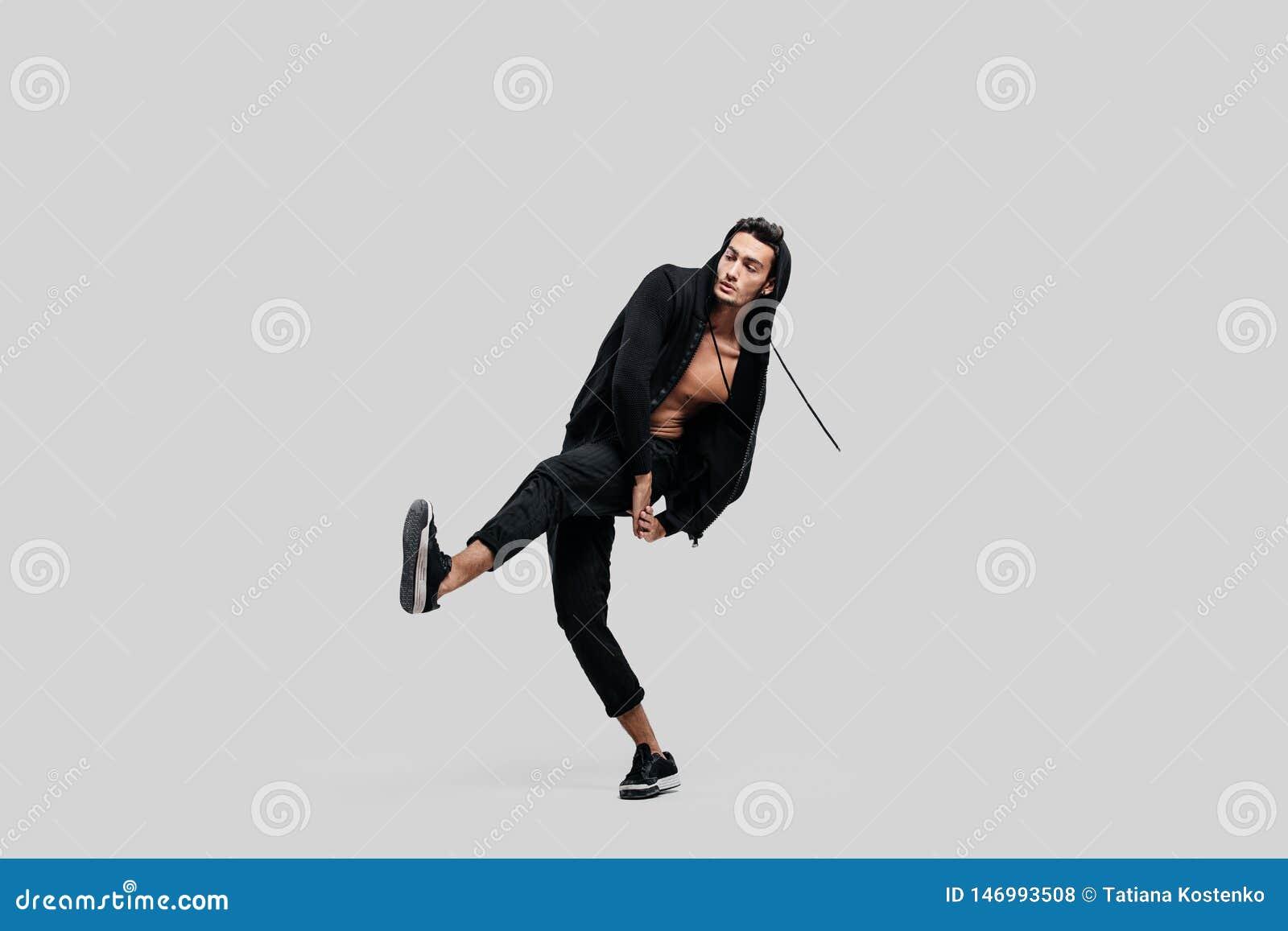 Lyfter iklädda svarta flåsanden för stilig ung dansare, en tröja på en naken torso upp ett ben, medan dansa gatadans