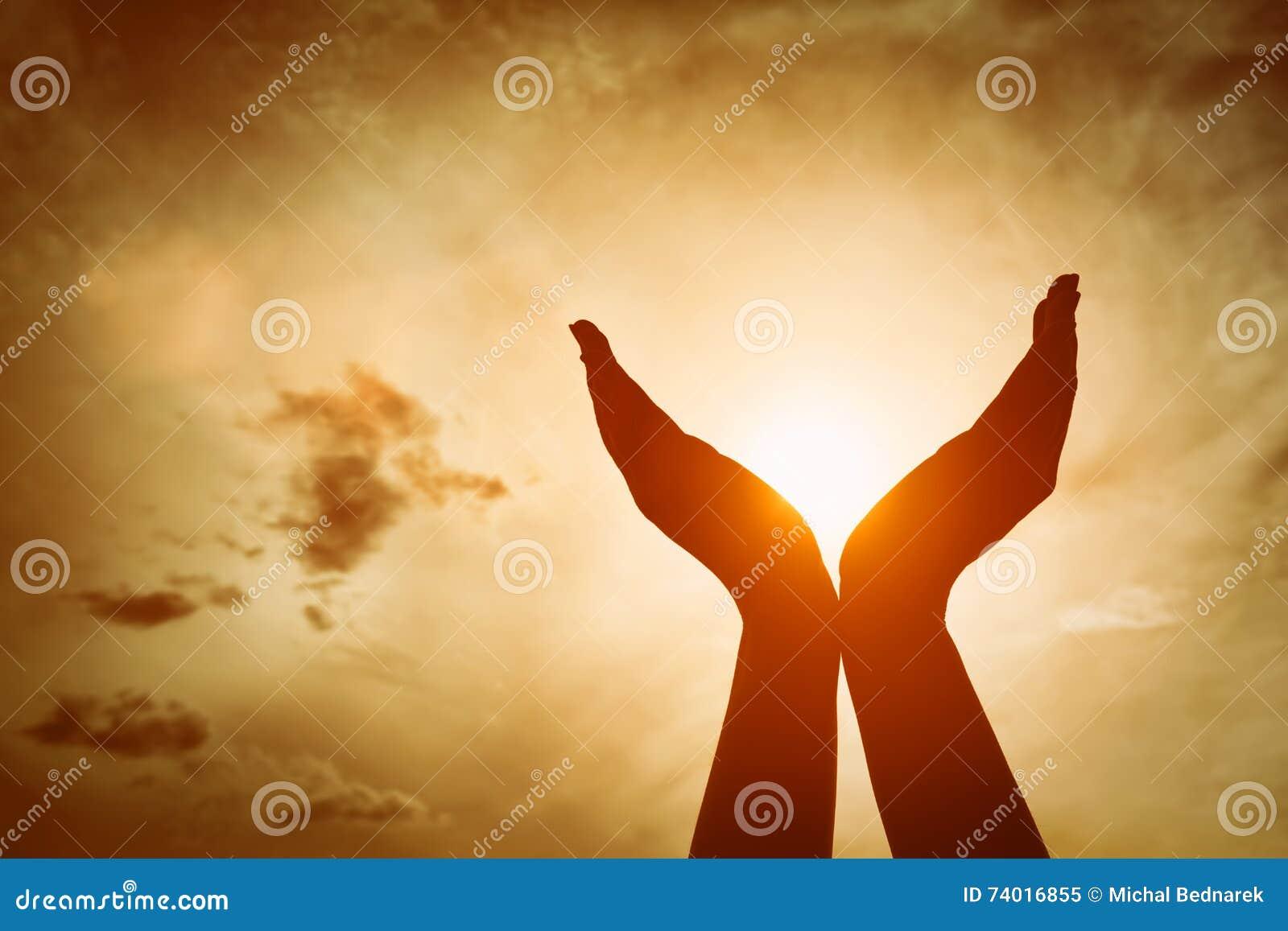 Lyftta händer som fångar solen på solnedgånghimmel Begrepp av andlighet, wellbeing, positiv energi
