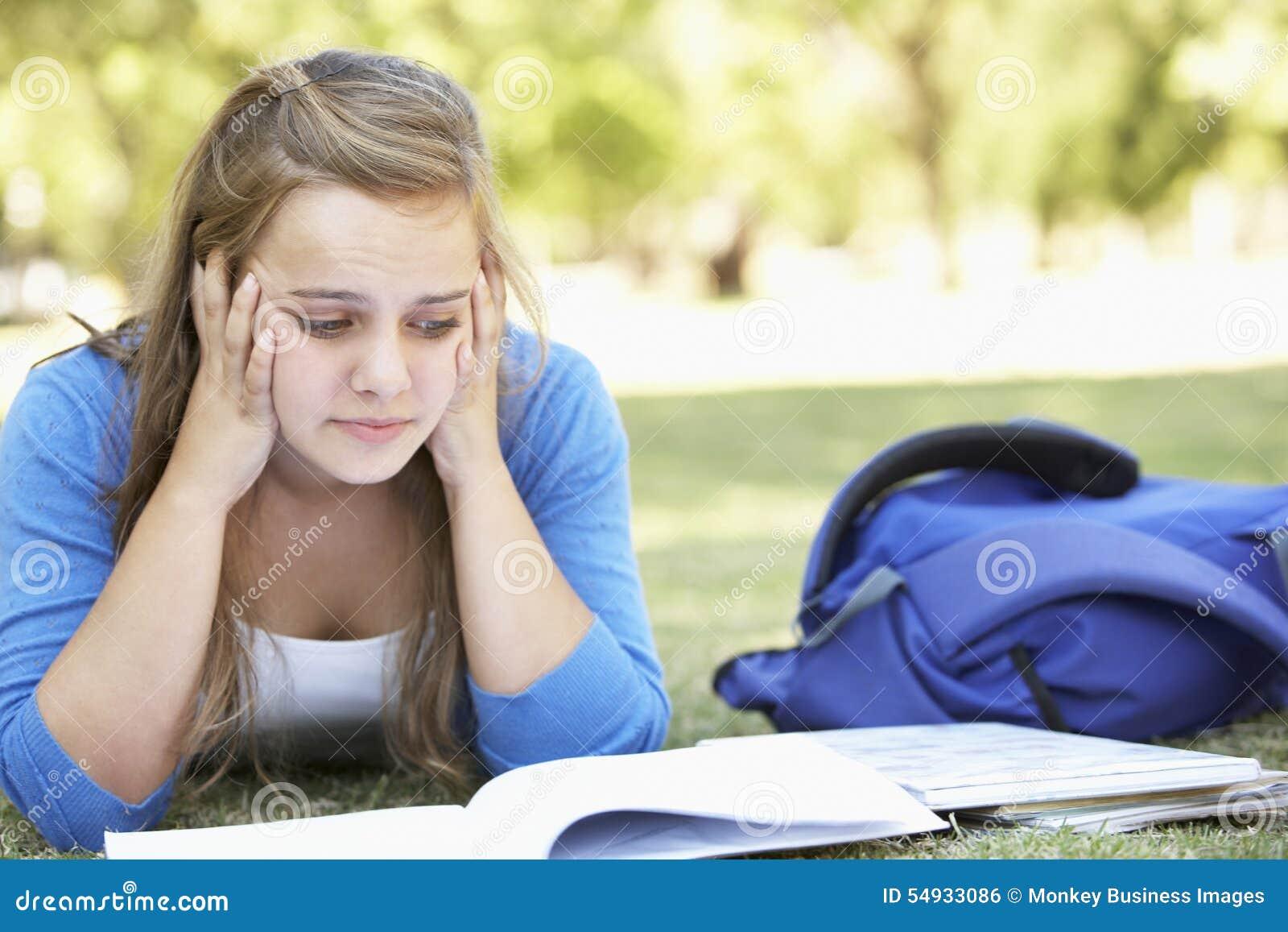 Lying In Park för kvinnlig högskolestudent läs- lärobok