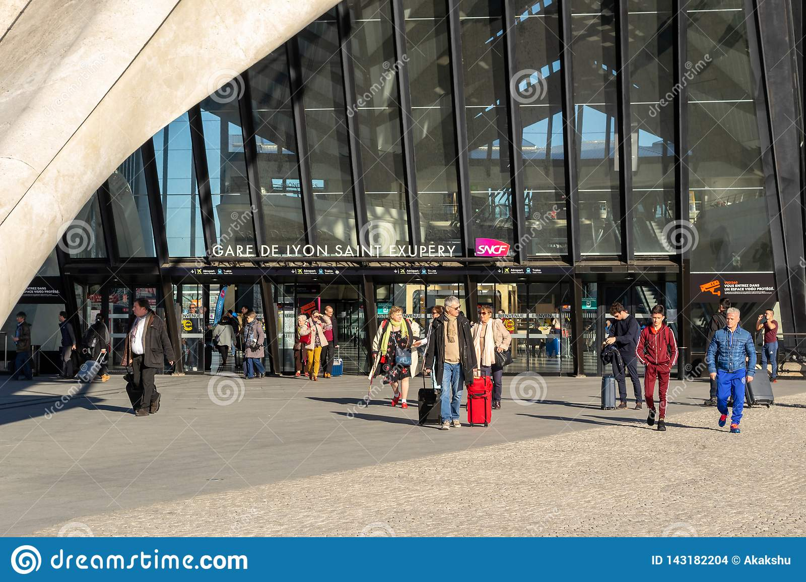 People arriving and departing at Gare de Lyon Saint Exupery SNCF main station, with carry on bags