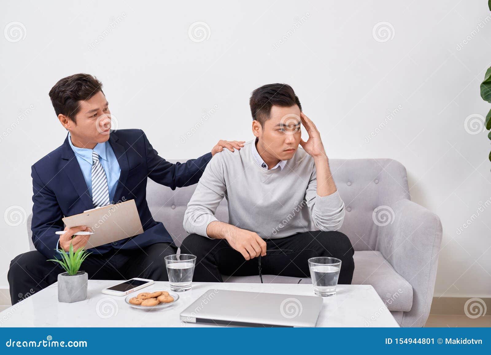 Lyssna till mig Asiatisk man som rynkar pannan, medan se hans terapeut