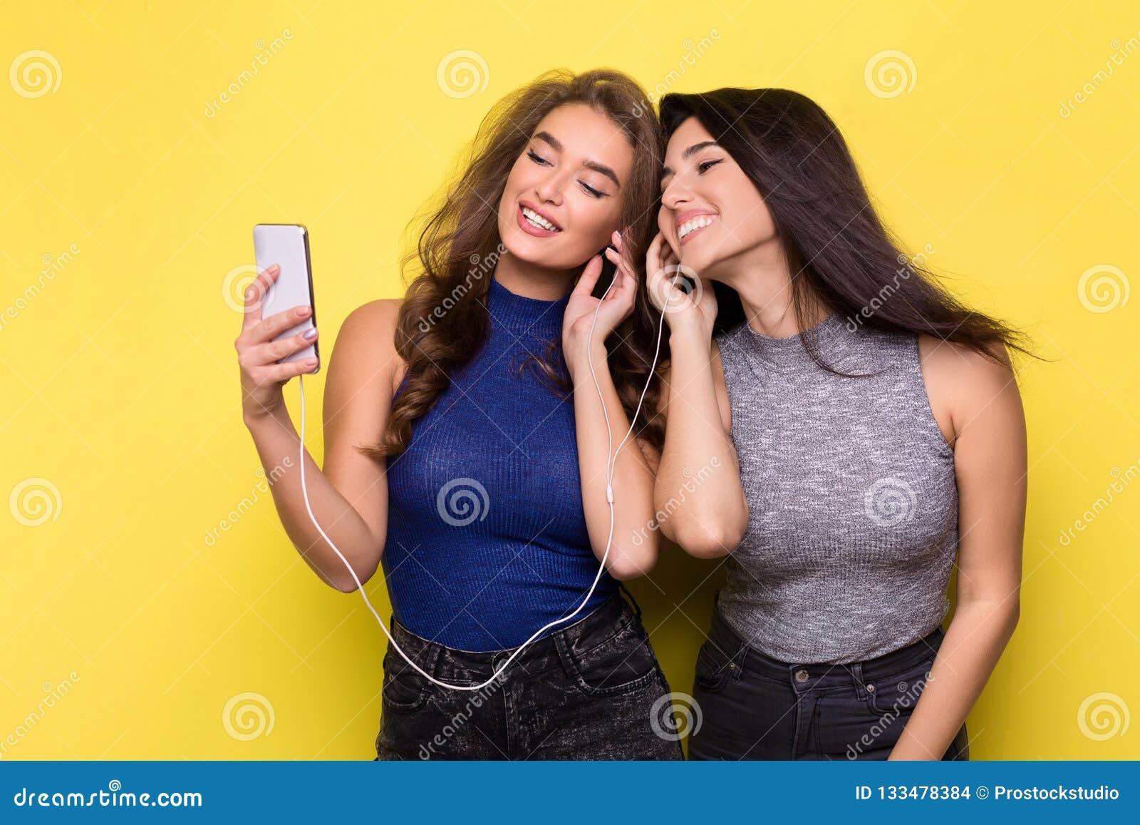 Lyssnande musik för två kvinnor som är online- på smartphonen