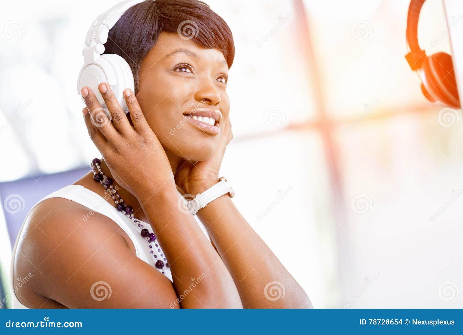 Lyssnande musik för ung härlig affärskvinna i hörlurar