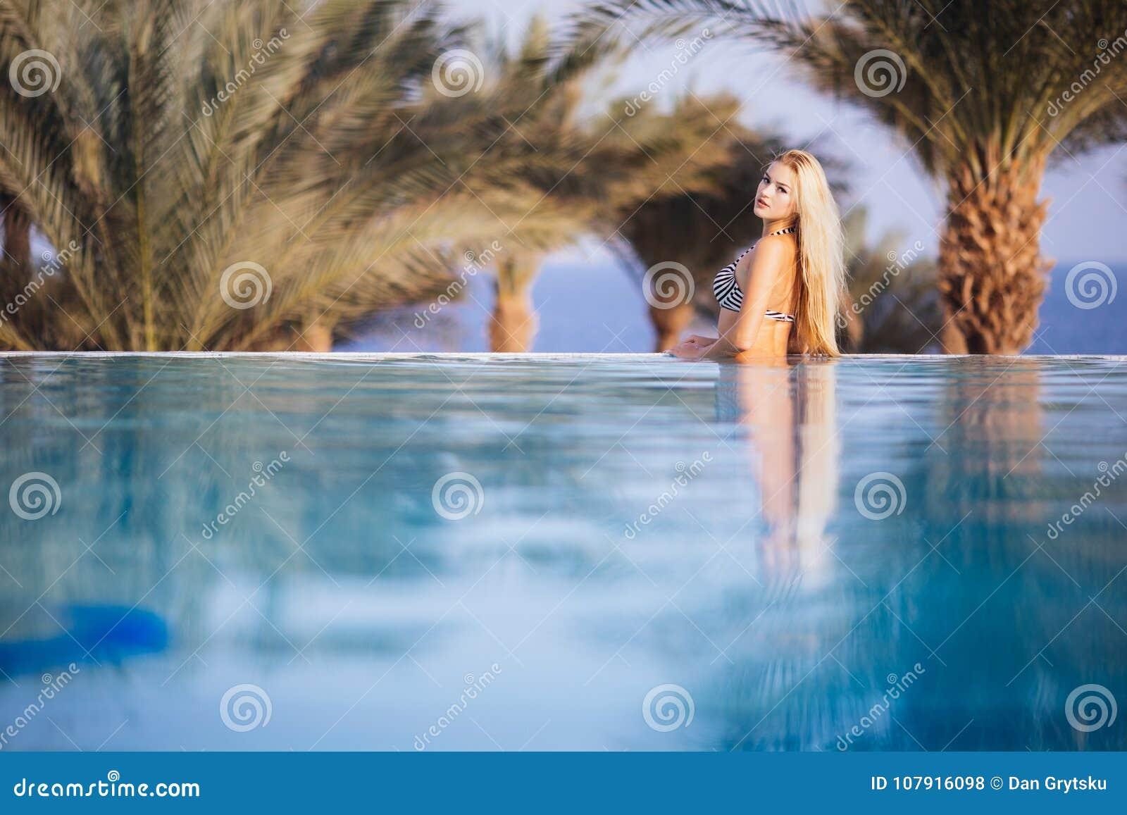 Lyxig semesterort Kvinna som kopplar av i oändlighetssimbassängvatten Härlig lycklig sund kvinnlig modell Enjoying Summer Travel