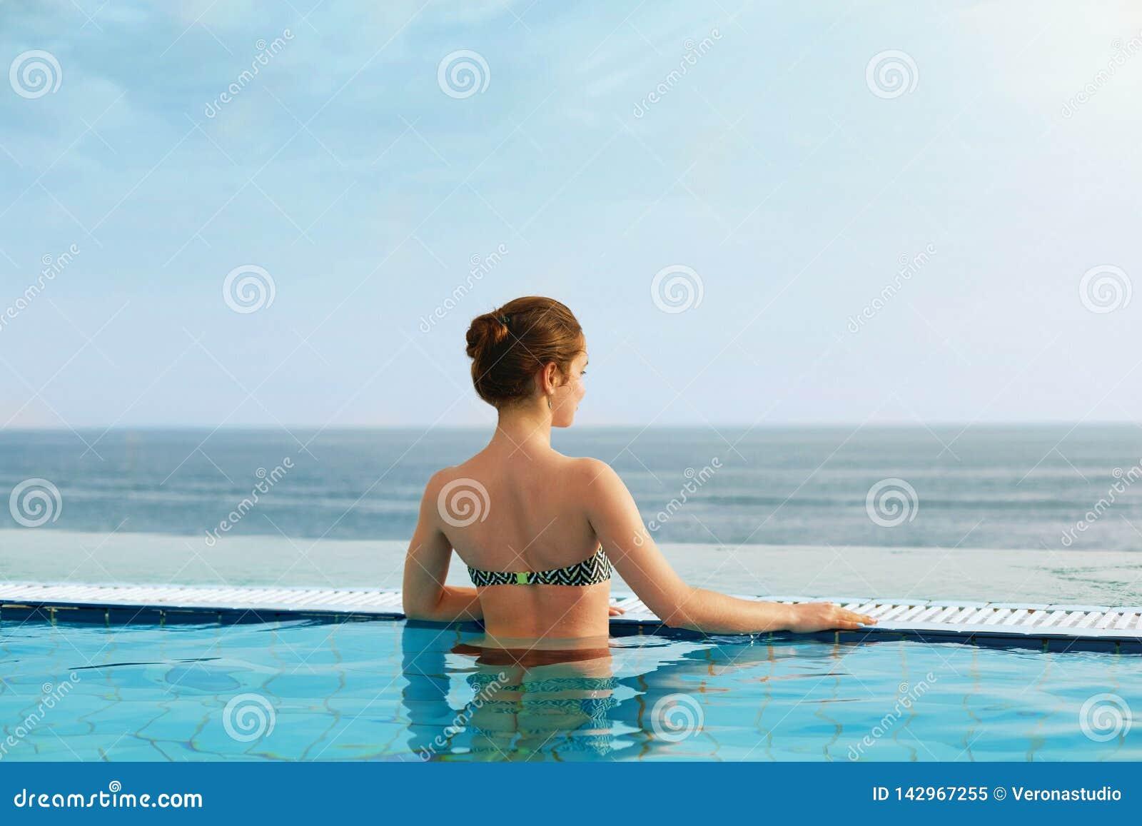 Lyxig semesterort Kvinna som kopplar av i o?ndlighetssimbass?ngvatten H?rlig lycklig sund kvinnlig modell Enjoying Summer Travel