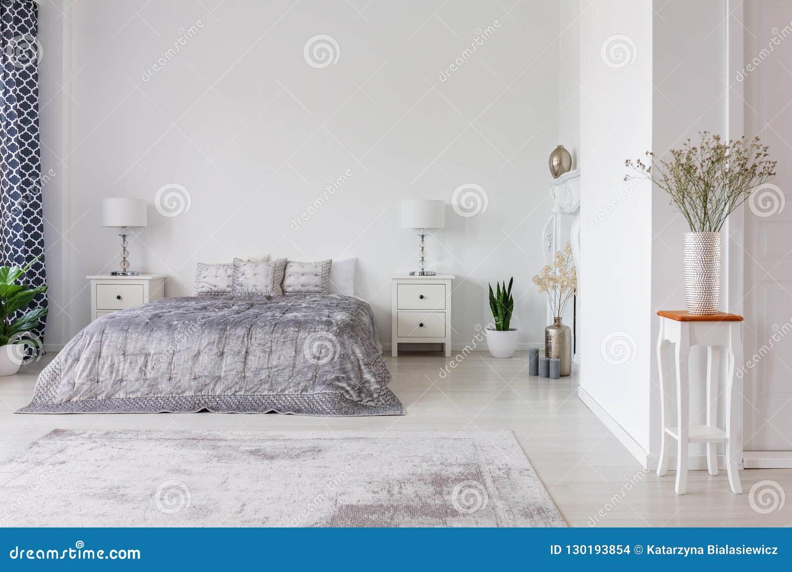 Lyxig sovruminredesign med silverduntäcket och kuddar på snäll formatsäng, verkligt foto med kopieringsutrymme