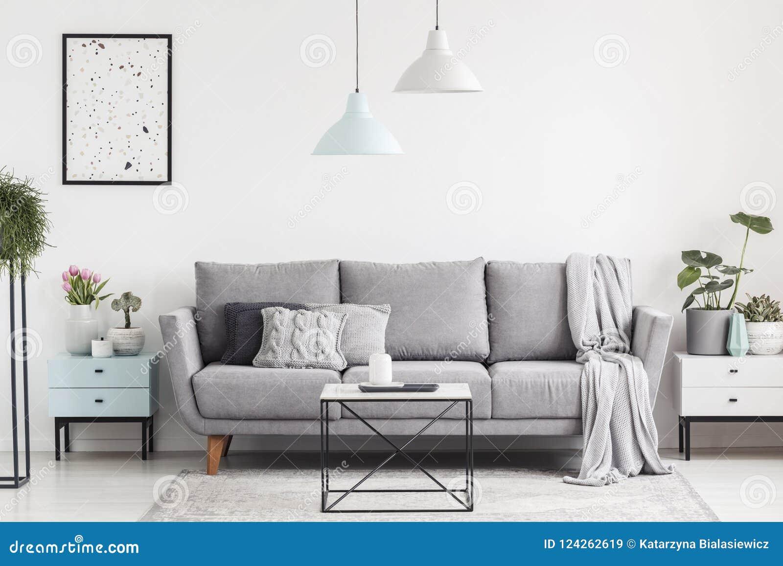 Lyxig vardagsruminre med en grå soffa, lampor, kaffe