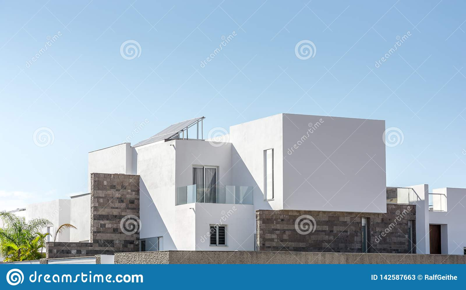 Lyxigt bostads- hus med modern arkitektur framme av solig himmel