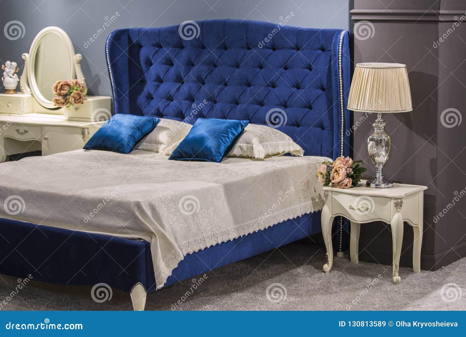 Lyxigt kungligt sovrum i antik stil med blå sammetsäng och vitnightstand