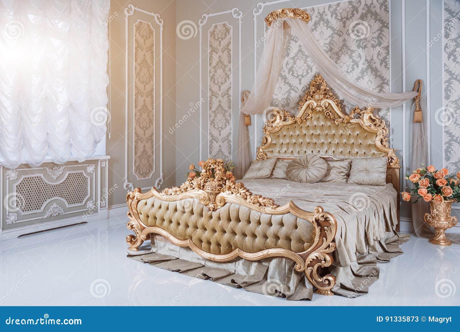 Lyxigt sovrum i ljusa färger med guld- möblemangdetaljer Stor bekväm dubbel kunglig säng i elegant klassiker