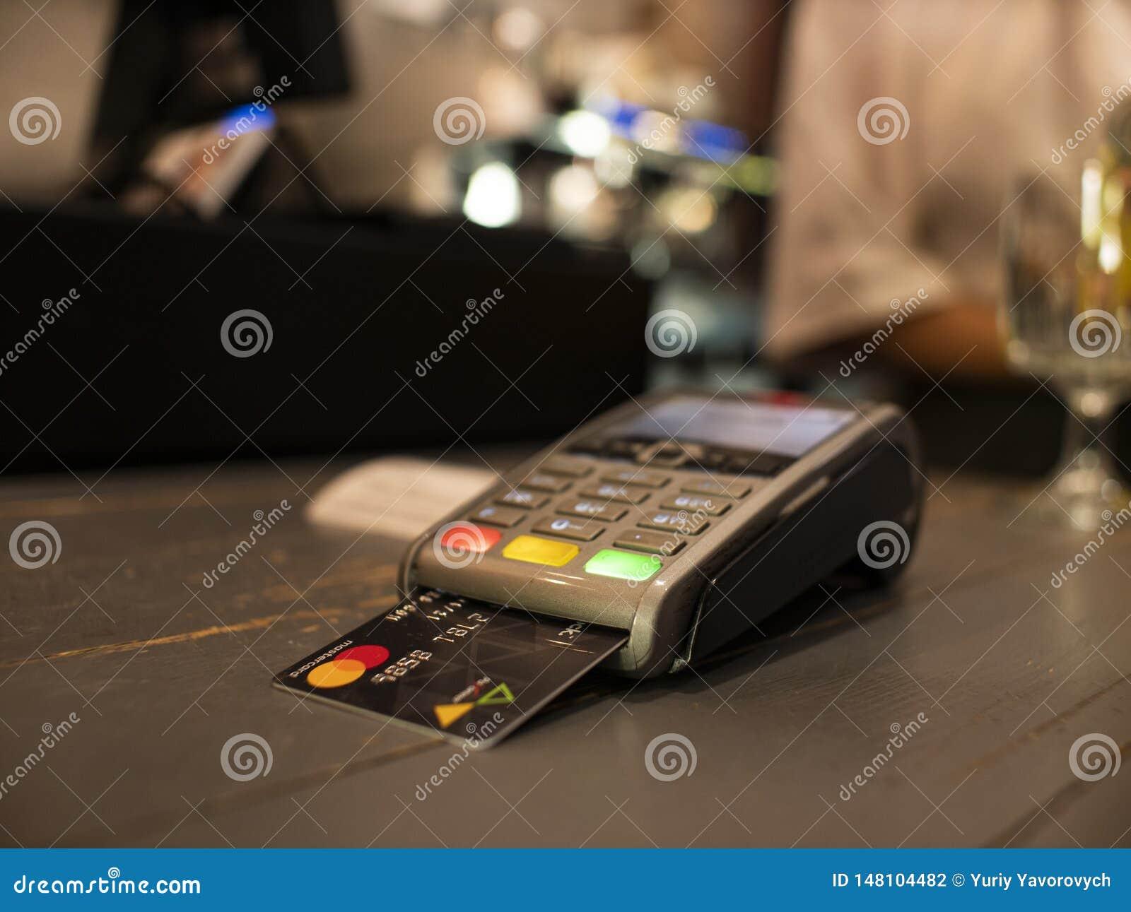 Máquina ascendente próxima do pagamento na tabela para a conta pagando perto na tabela Terminal sem fio da posi??o com cart?o