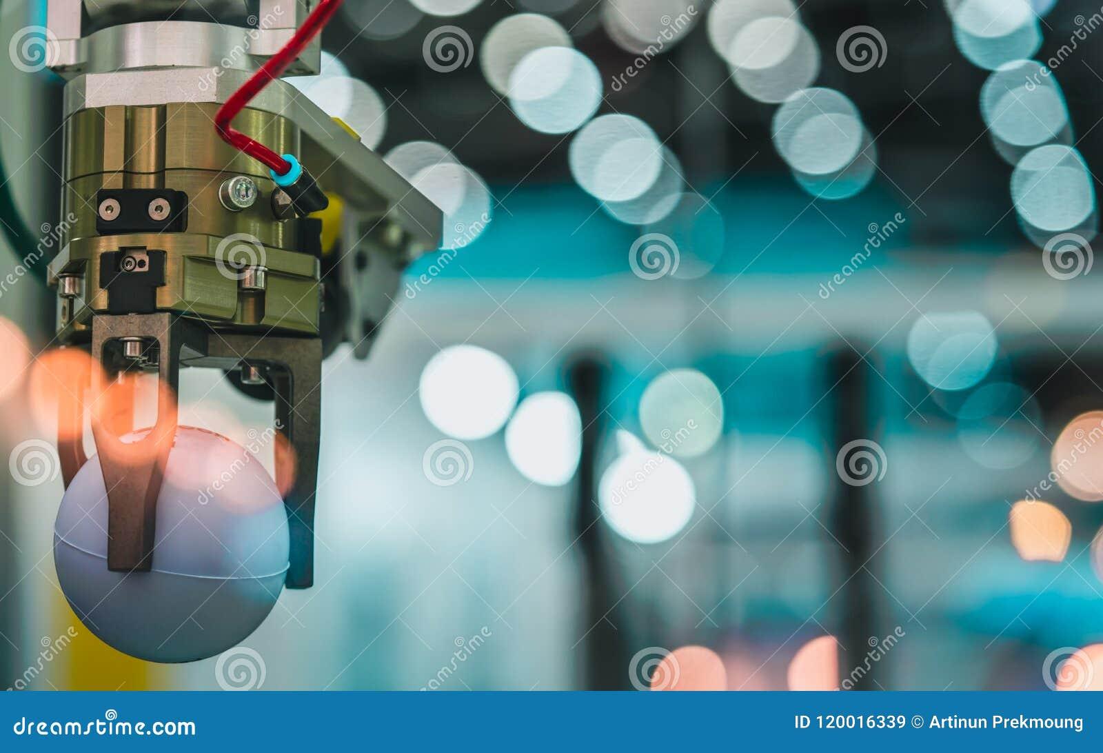 A máquina da mão do robô do close up que pegara a bola branca no bokeh borrou o fundo Use o robô esperto na indústria de transfor