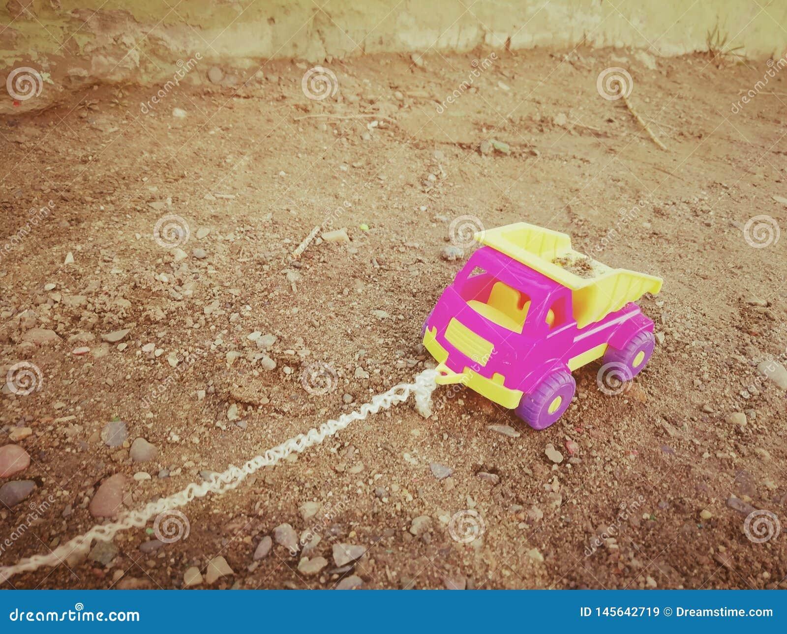 A máquina das crianças com uma corda na caixa de areia